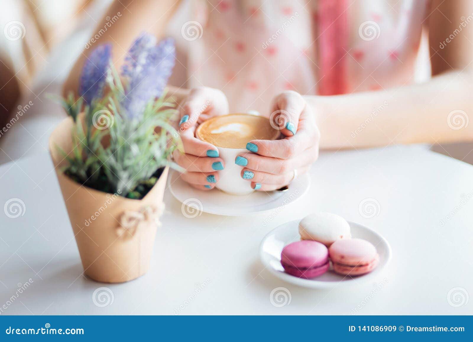 La donna passa la tenuta della tazza di caffè Macarons sulla tavola e sulla lavanda