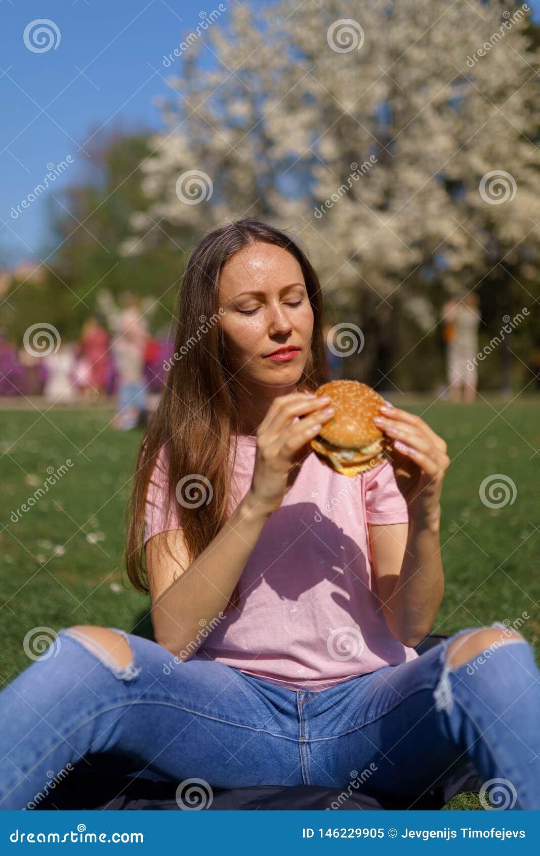 La donna riuscita di affari che mangia il cheesburger dell hamburger degli alimenti a rapida preparazione gode del suo tempo libe
