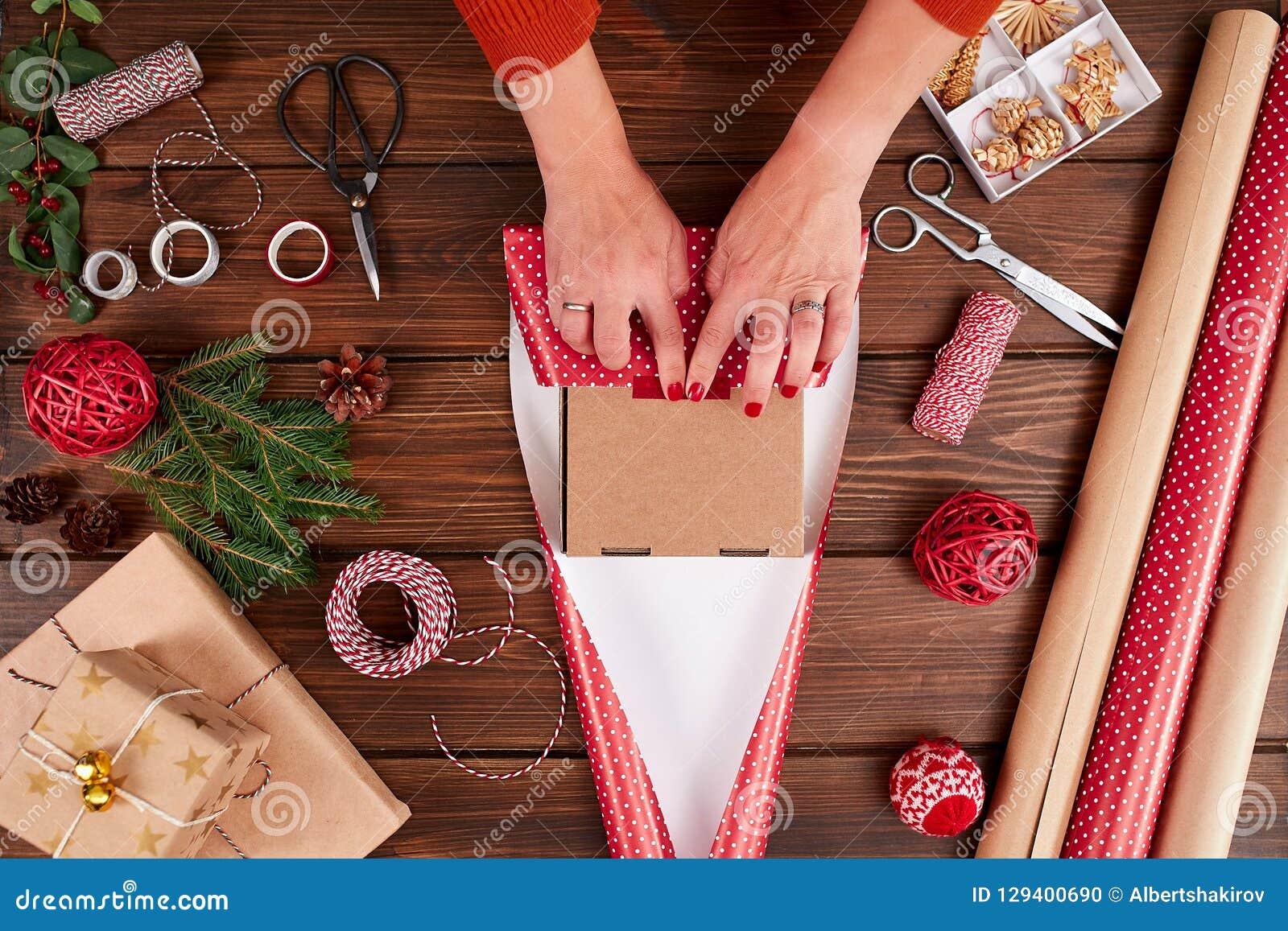 La donna s passa lo spostamento del regalo di Natale su fondo di legno scuro
