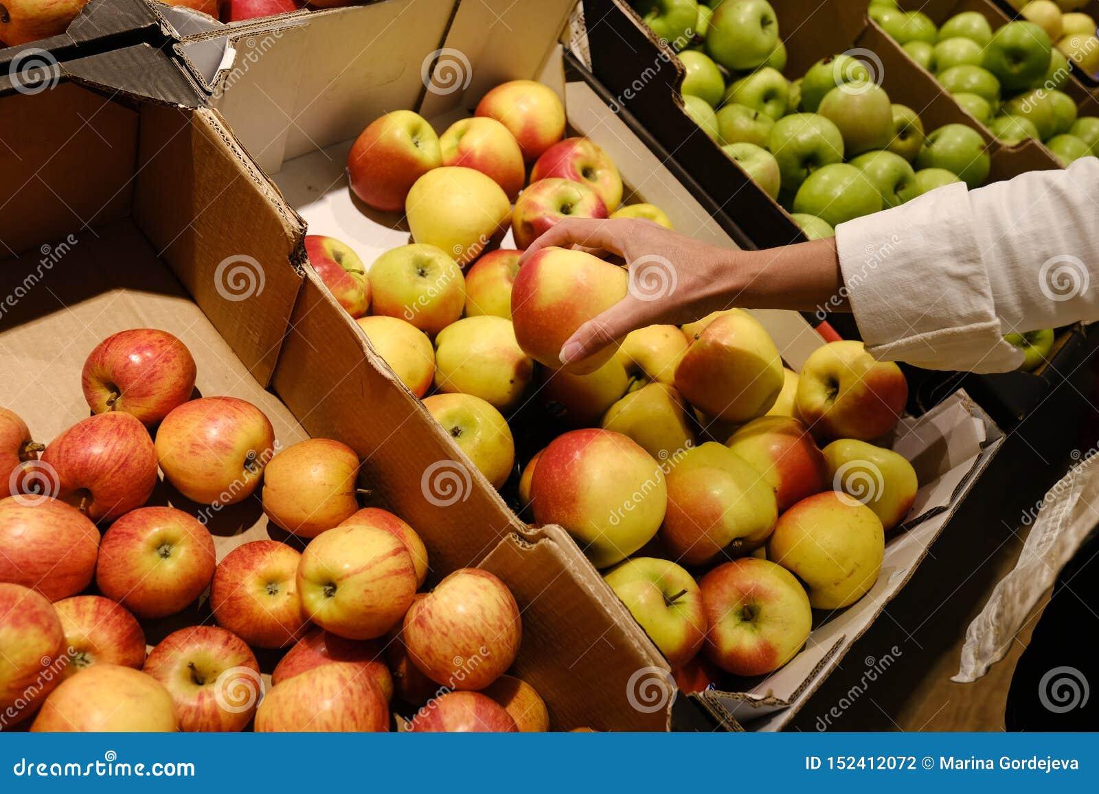 La donna sceglie le mele nel deposito contatore in mele in un supermercato