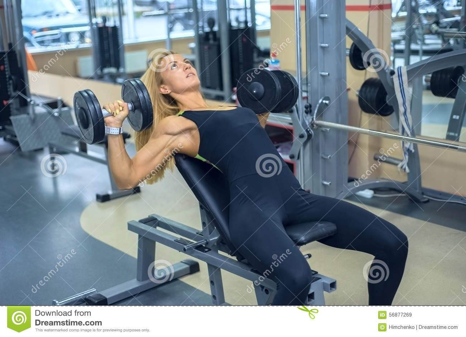La donna scuote i suoi muscoli pettorali in palestra