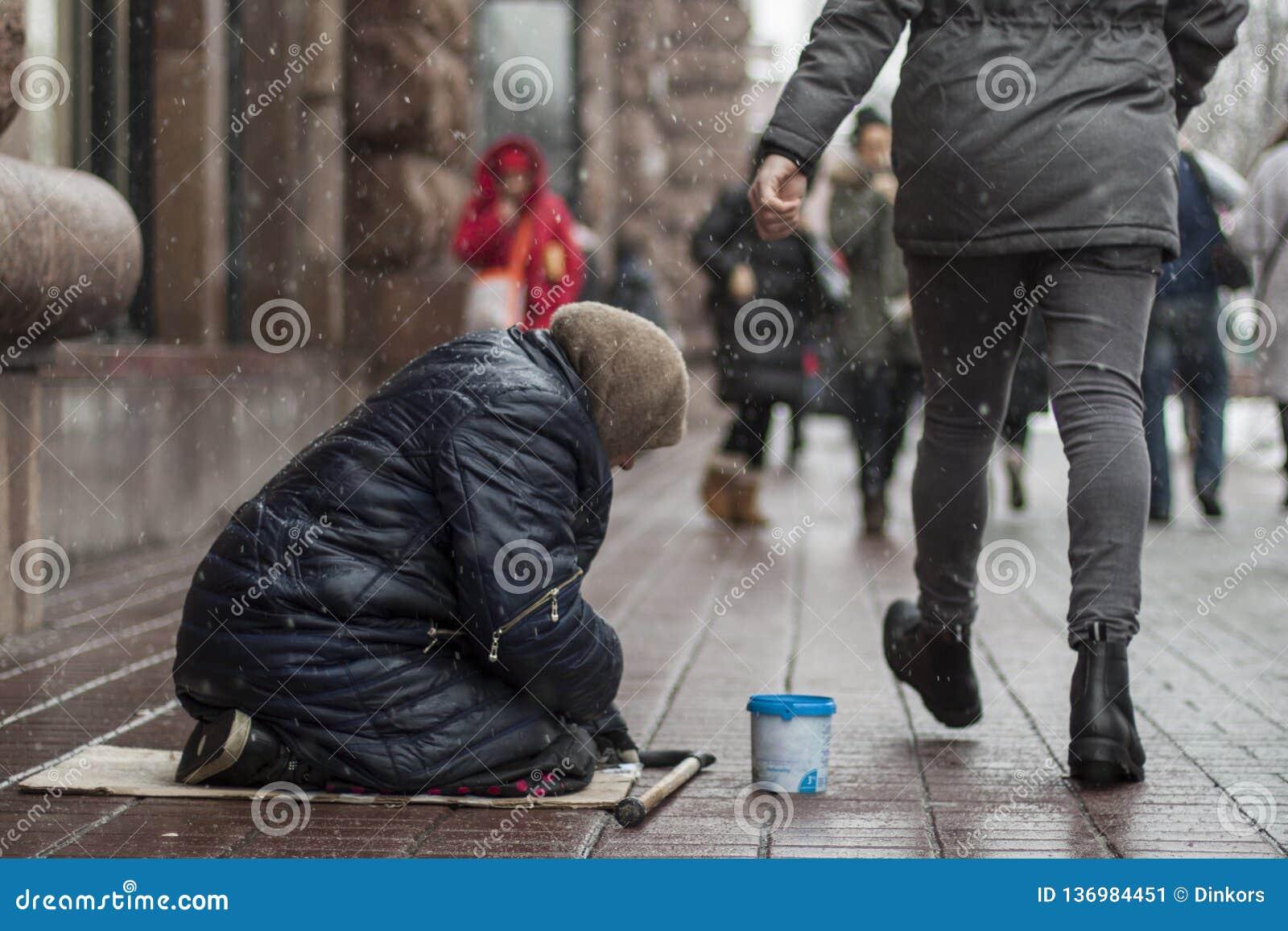 La donna senza tetto affamata del mendicante elemosina soldi sulla via urbana nella città dalla gente che cammina vicino, concett