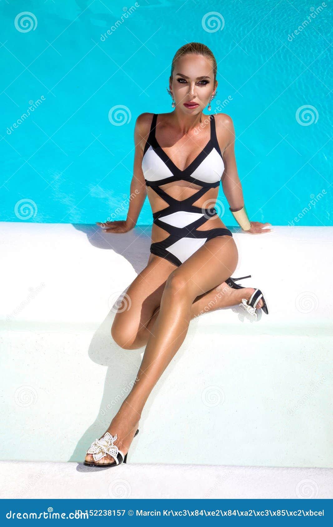 La donna sexy elegante in bikini di lusso sul corpo esile e ben fatto Sun-abbronzato sta posando vicino alla piscina Prendere il