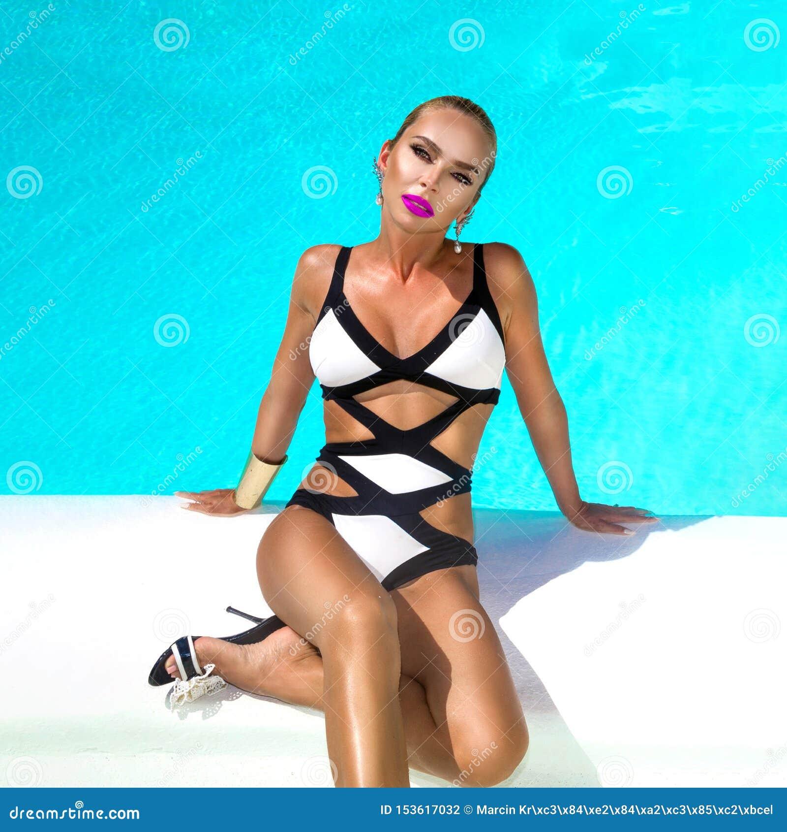 La donna sexy elegante nel bikini in bianco e nero sul corpo esile e ben fatto Sun-abbronzato sta posando vicino alla piscina - i