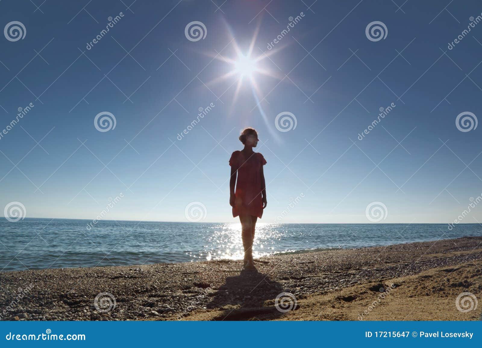 La donna si leva in piedi a secco di fronte al sole