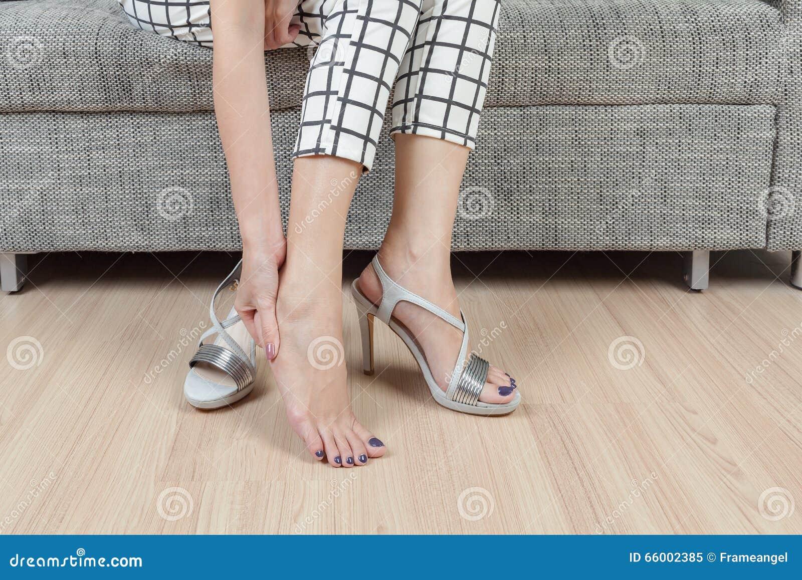 La donna si siede sulla sedia e la mano femminile con dolore del piede dopo, prende SH