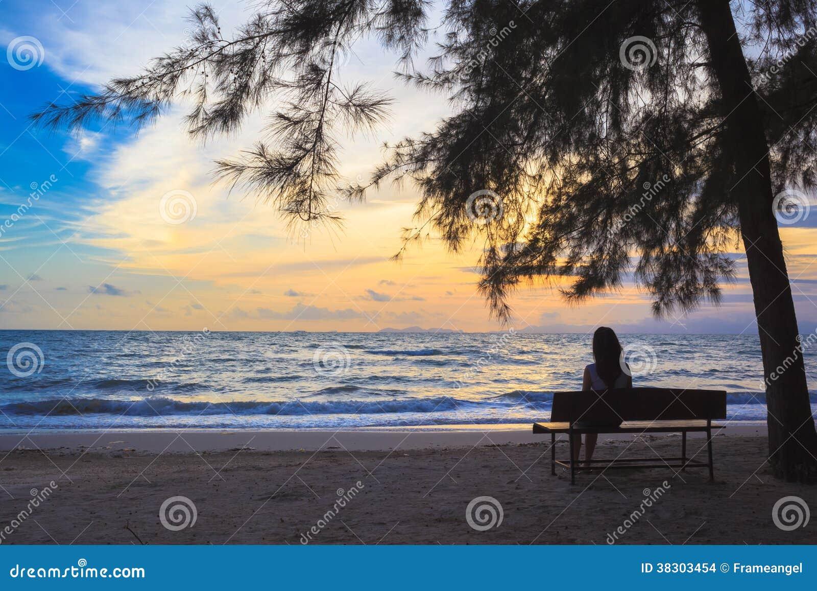 La donna si siede sulle sedie sotto l albero sulla spiaggia