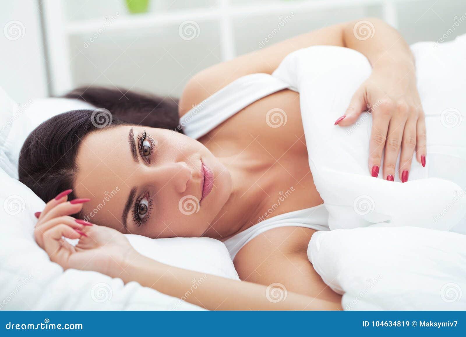 La donna si sveglia da sonno lungo a letto che sbadiglia e che allunga nella t