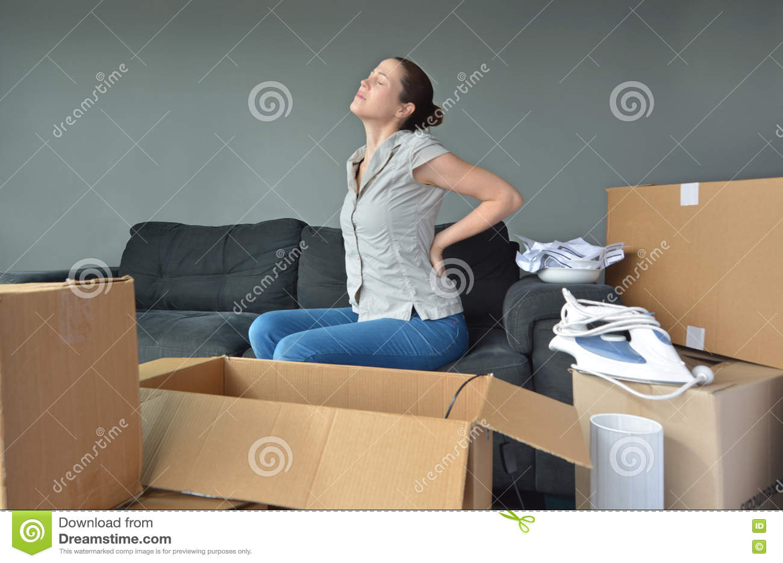 La donna soffre da dolore alla schiena dovuto il disimballaggio delle scatole