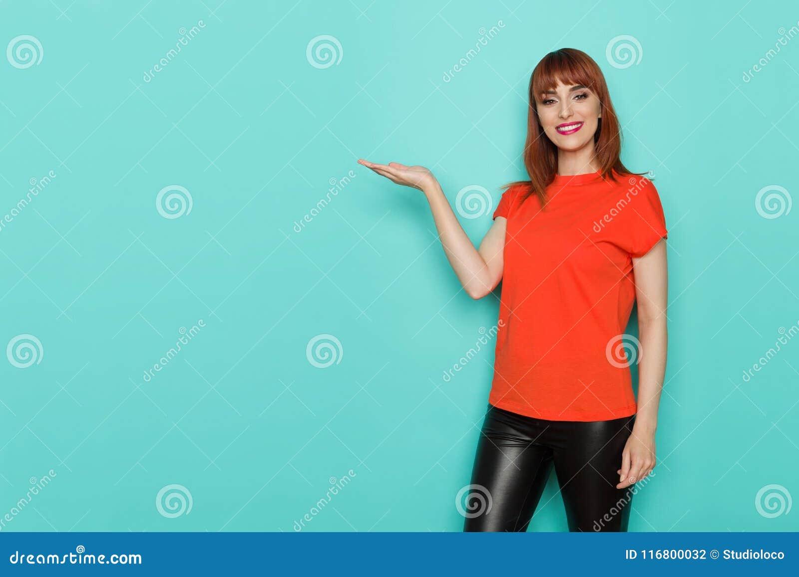 La donna sorridente in camicia arancio sta presentando qualcosa