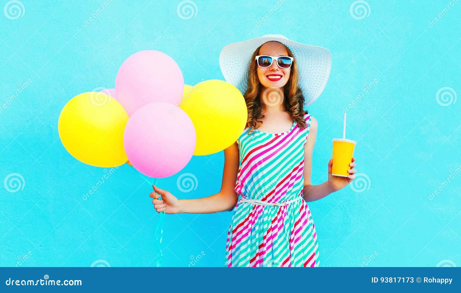 La donna sorridente graziosa di modo tiene una tazza del succo di frutta con i palloni variopinti di un aria