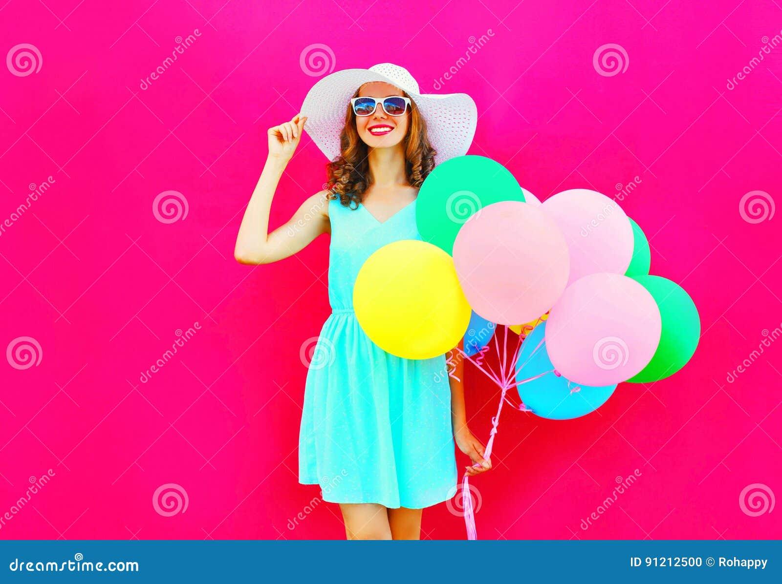 La donna sorridente graziosa felice di modo con i palloni variopinti di un aria sta divertendosi portando un cappello di paglia d