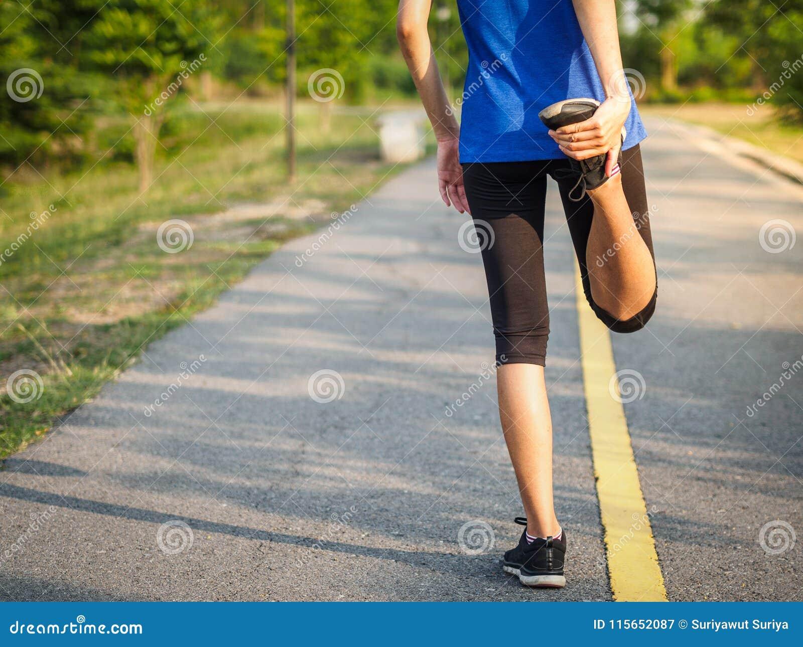 La donna sta allungando prima di pareggiare Concep di stile di vita e di forma fisica