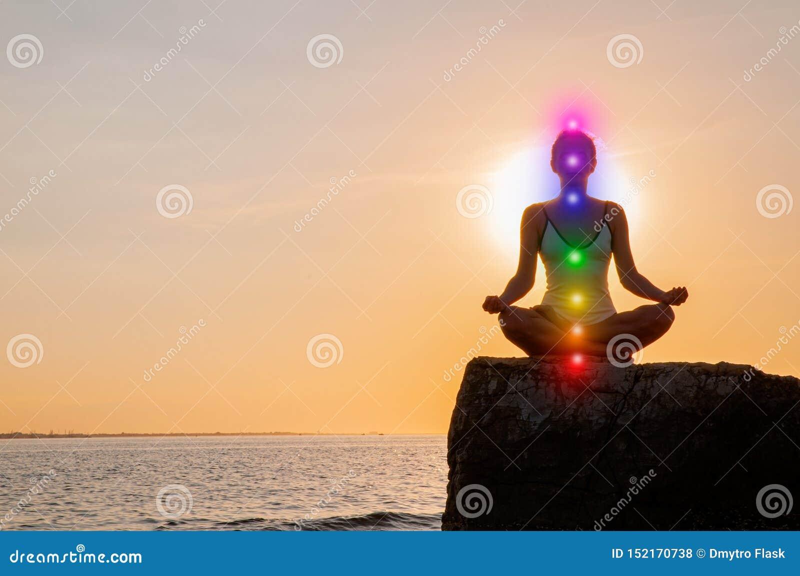 La donna sta meditando con l ardore sette chakras su pietra al tramonto La siluetta della donna sta praticando l yoga sulla spiag