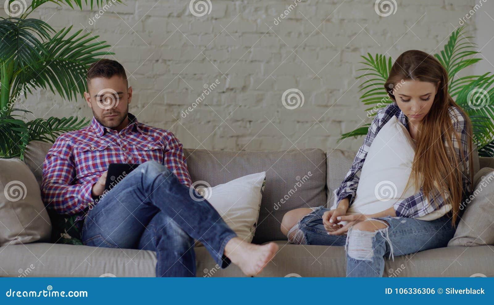La donna turbata dei giovani è sollecitata ed infelice mentre il suo ragazzo che per mezzo del computer della compressa si siede