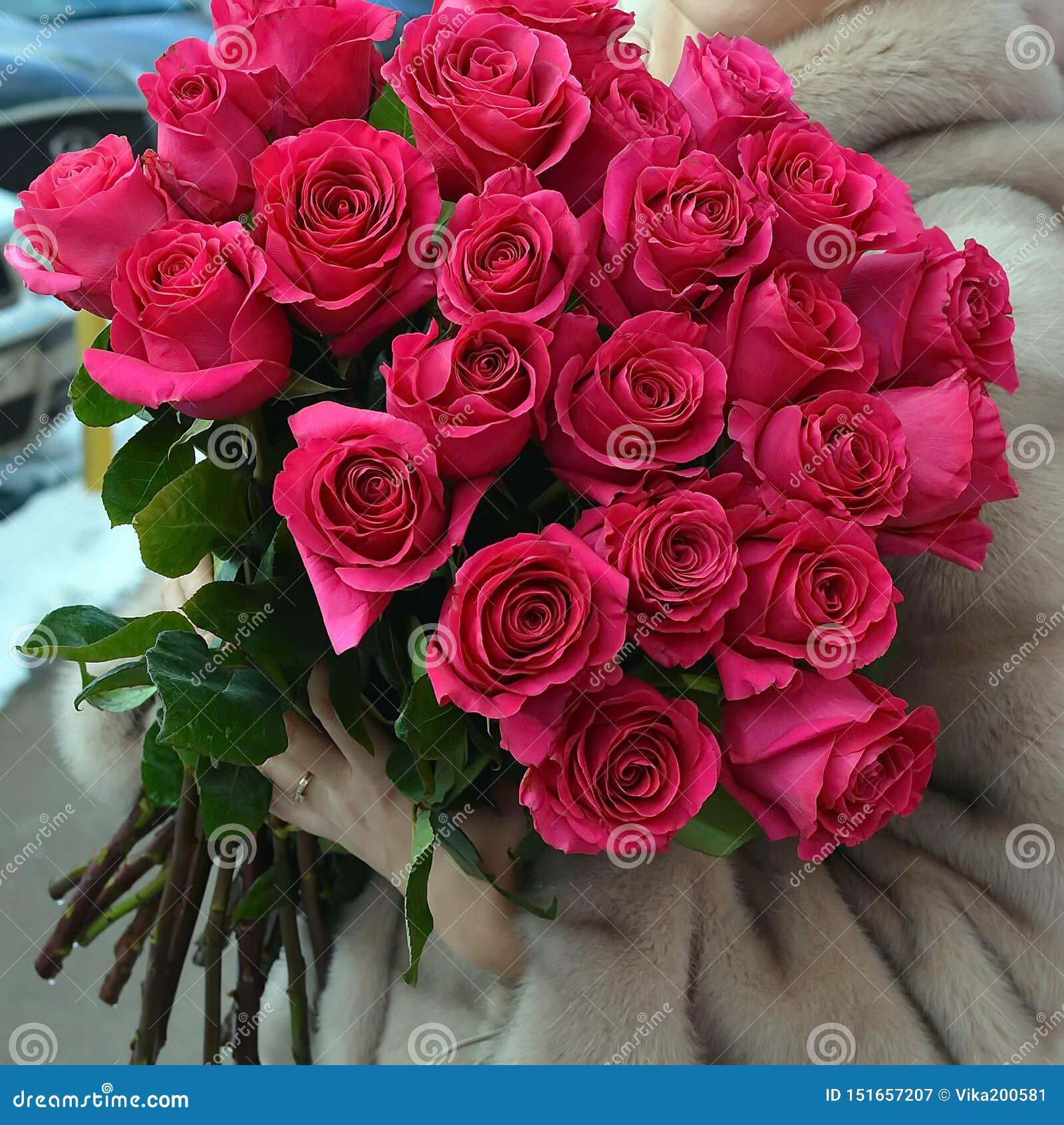 La donna in una pelliccia con un mazzo enorme delle rose