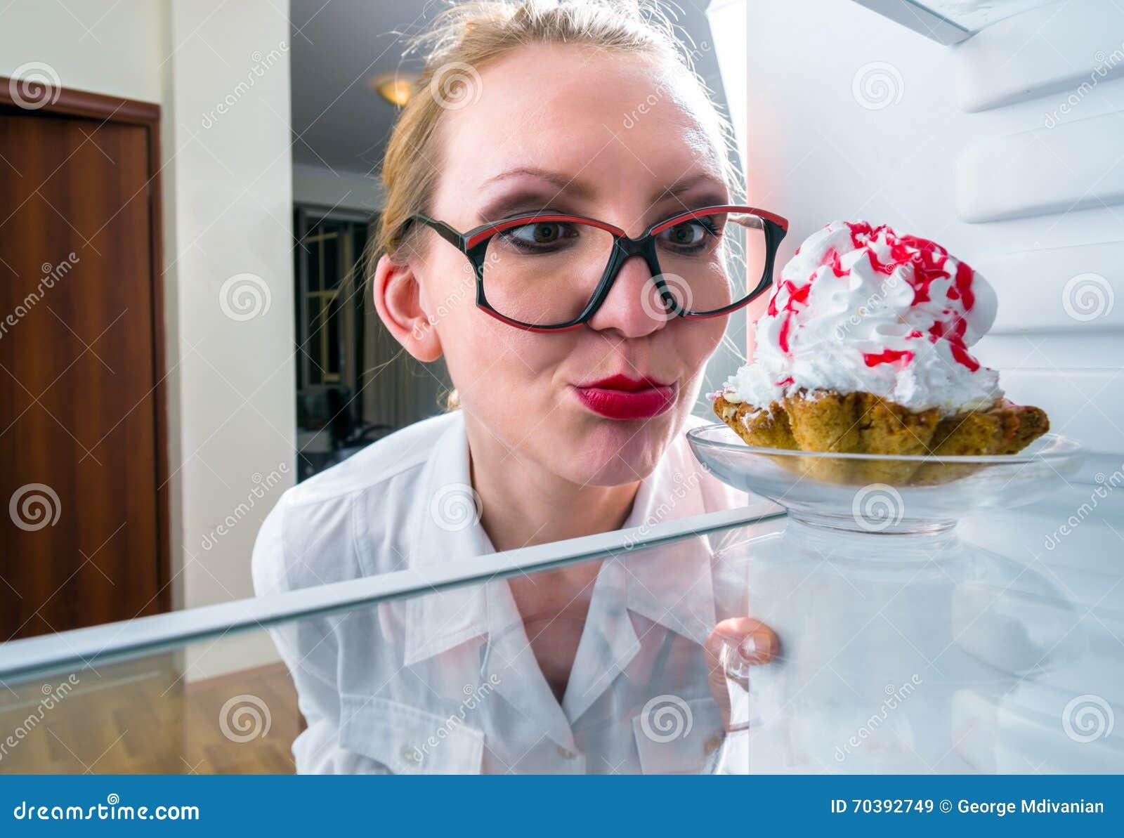 La donna vede il dolce dolce in frigorifero