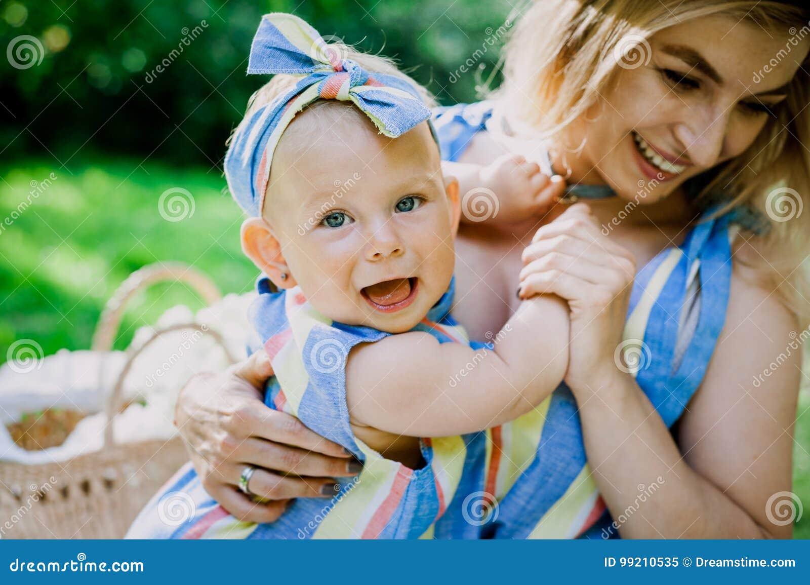 La donna in vestito blu alza sulla sua piccola figlia negli stessi vestiti