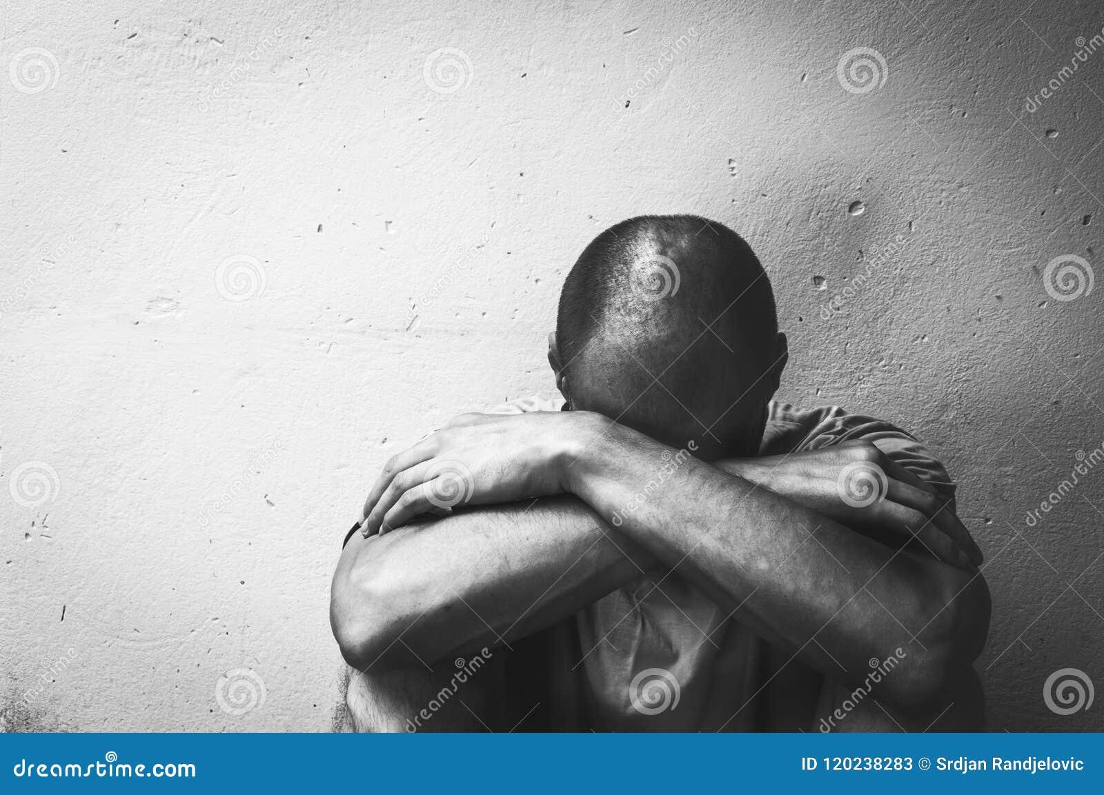 La droga y el alcohol sin hogar del hombre envician sentarse solo y deprimido en la calle que siente concentrados documental ansi
