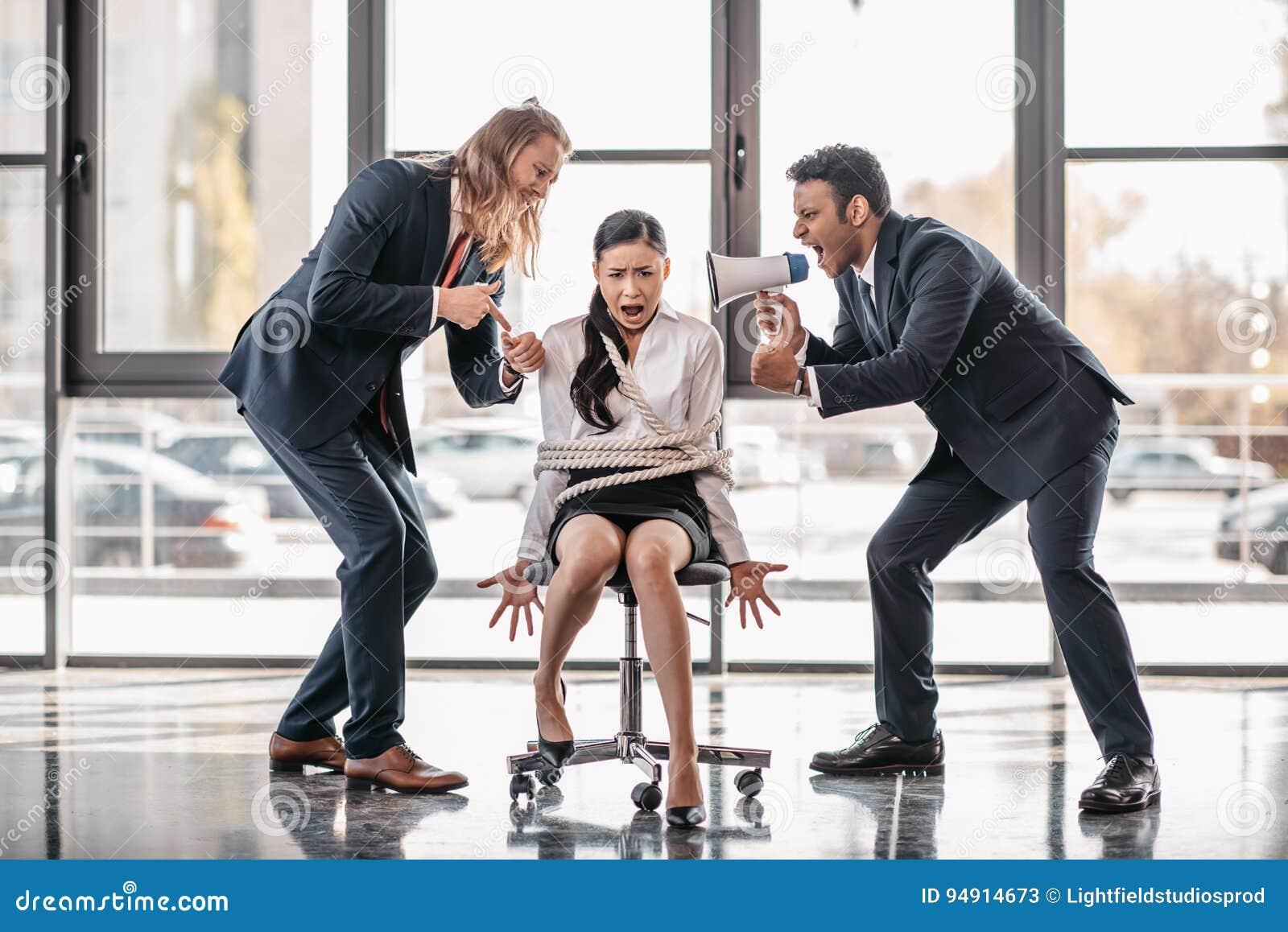 La empresaria asiática limita con la cuerda en silla mientras que los hombres de negocios que gritan en ella con el megáfono