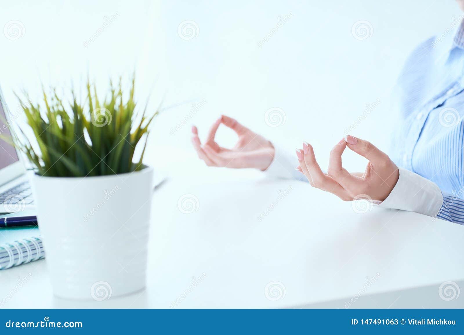 La empresaria de la calma que medita en el trabajo, foco en las manos femeninas en mudra, se cierra encima de la visión Empleado