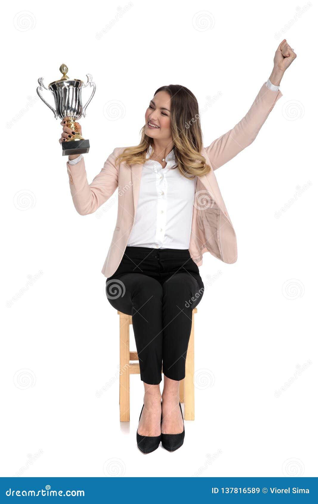 La empresaria feliz mira el trofeo y celebra mientras que se sienta