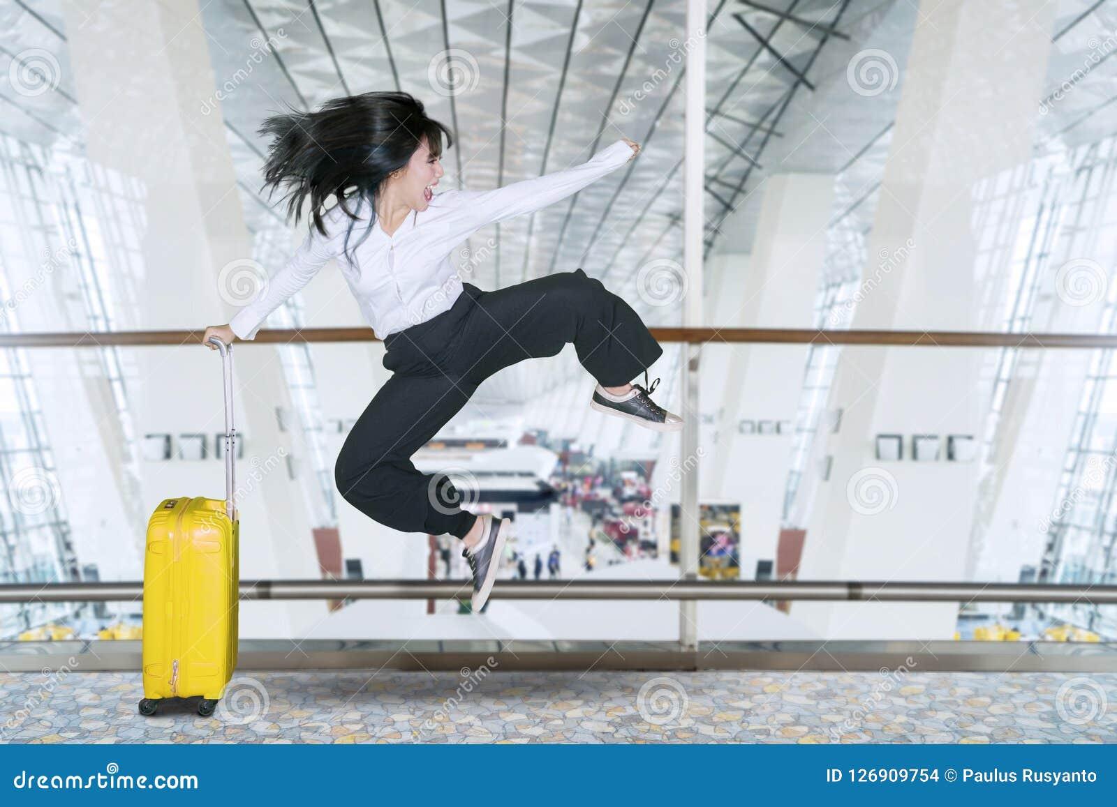 La empresaria feliz salta en el aeropuerto