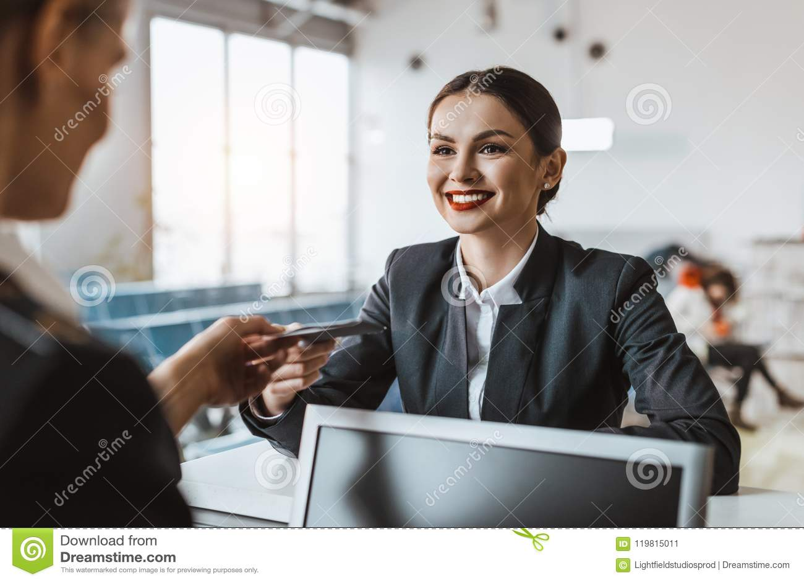 La empresaria joven atractiva que da el pasaporte y el boleto al personal en el aeropuerto comprueban
