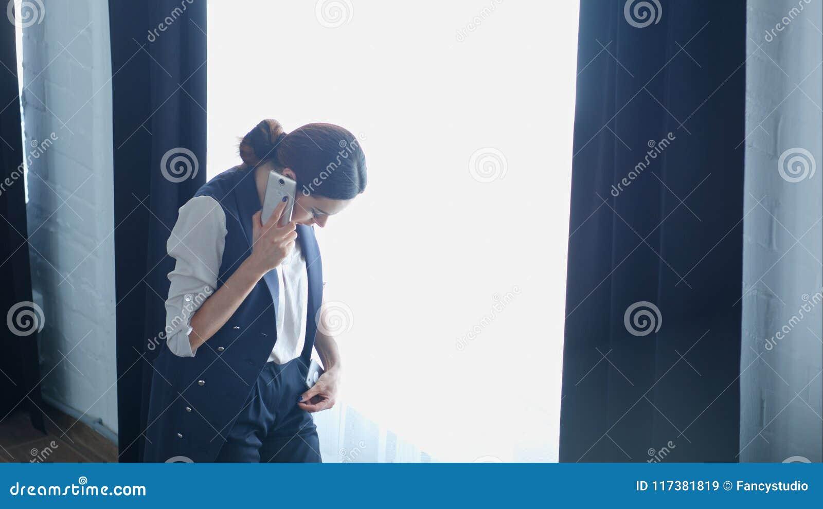 La empresaria orgullosa joven está hablando en su teléfono móvil con el cliente, mientras que coloca la ventana cercana de la ofi