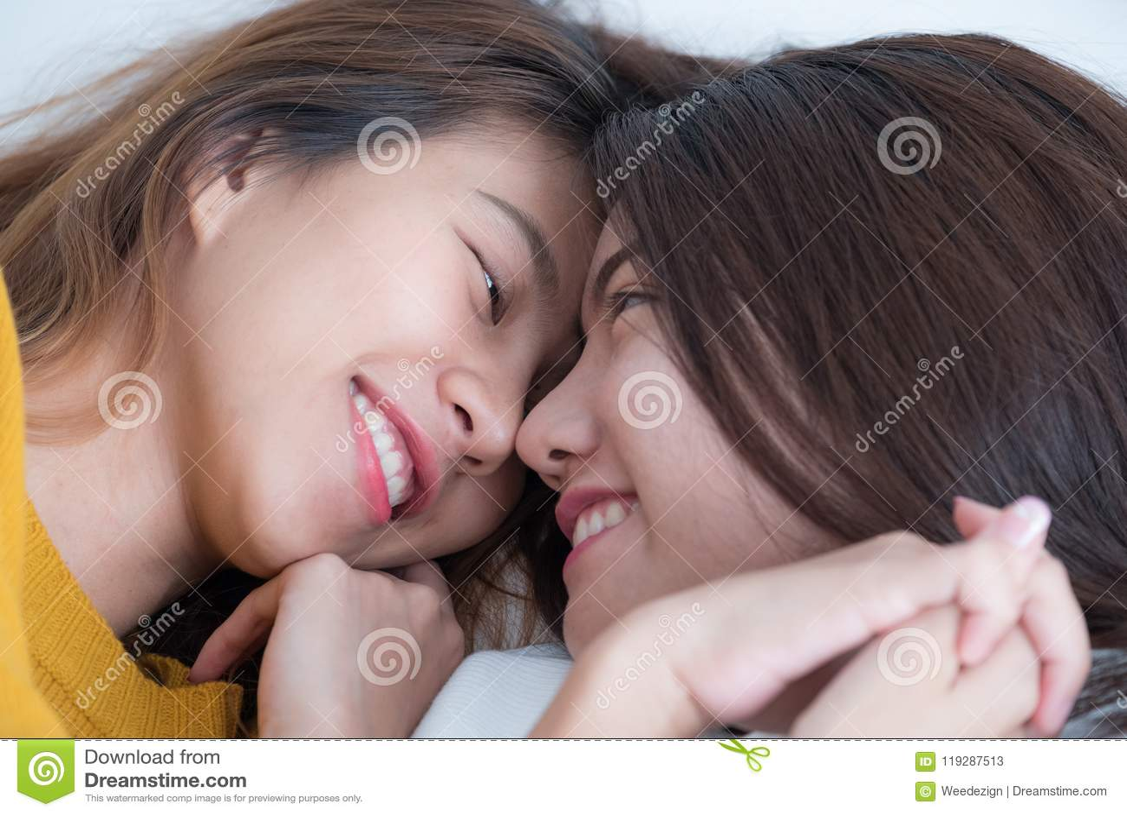 La endecha lesbiana de los pares de Asia LGBT en cama y el cierre observan con felicidad