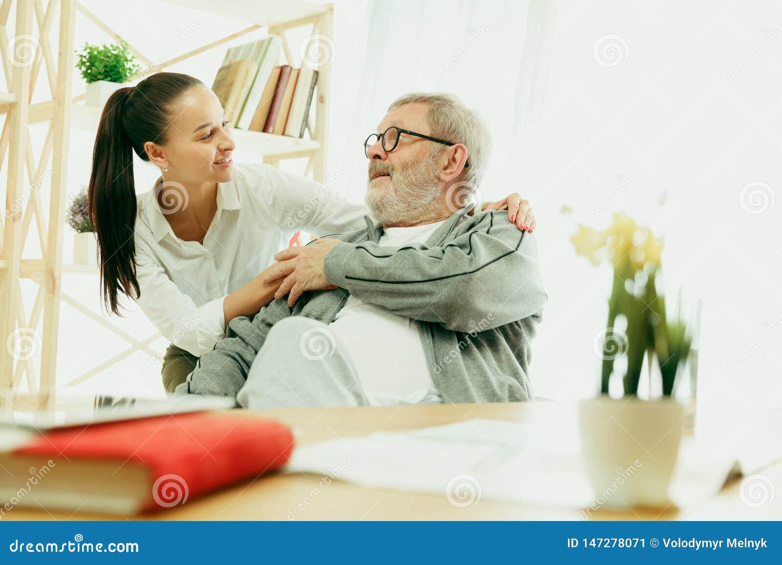 La enfermera que visita que toma cuidado del hombre mayor