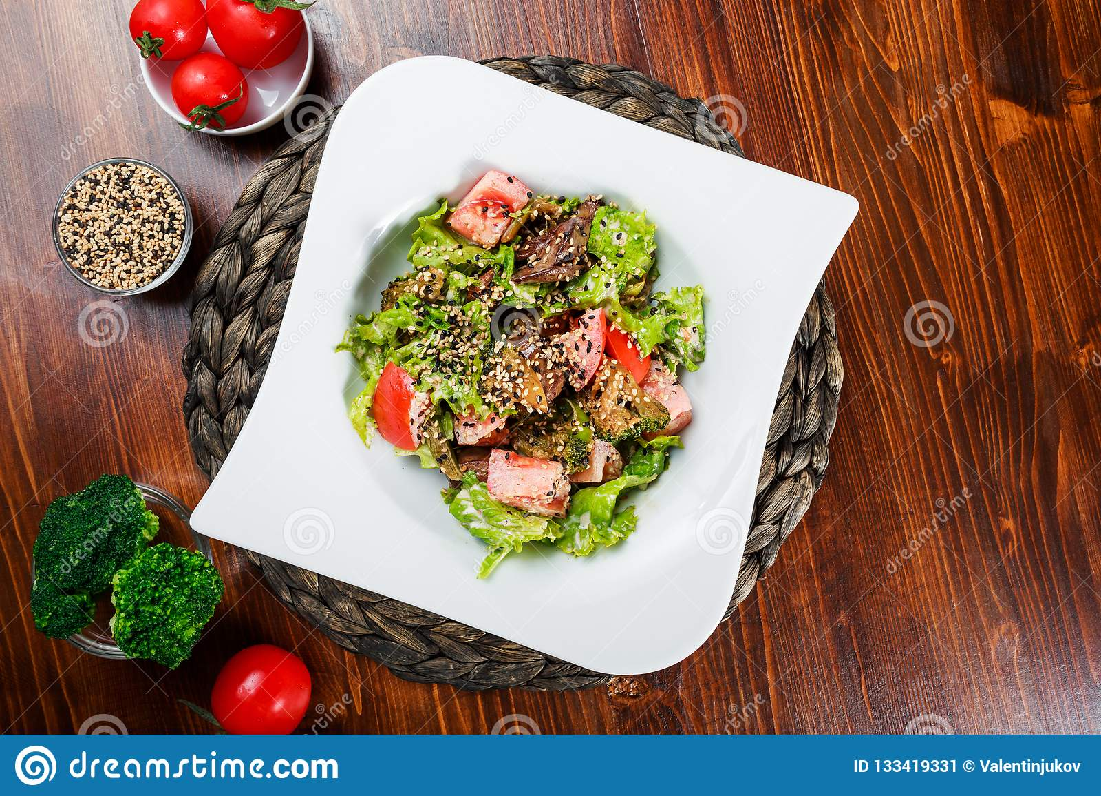 La ensalada caliente con el hígado de pollo, tomates, lechuga se va, bróculi en la tabla de madera