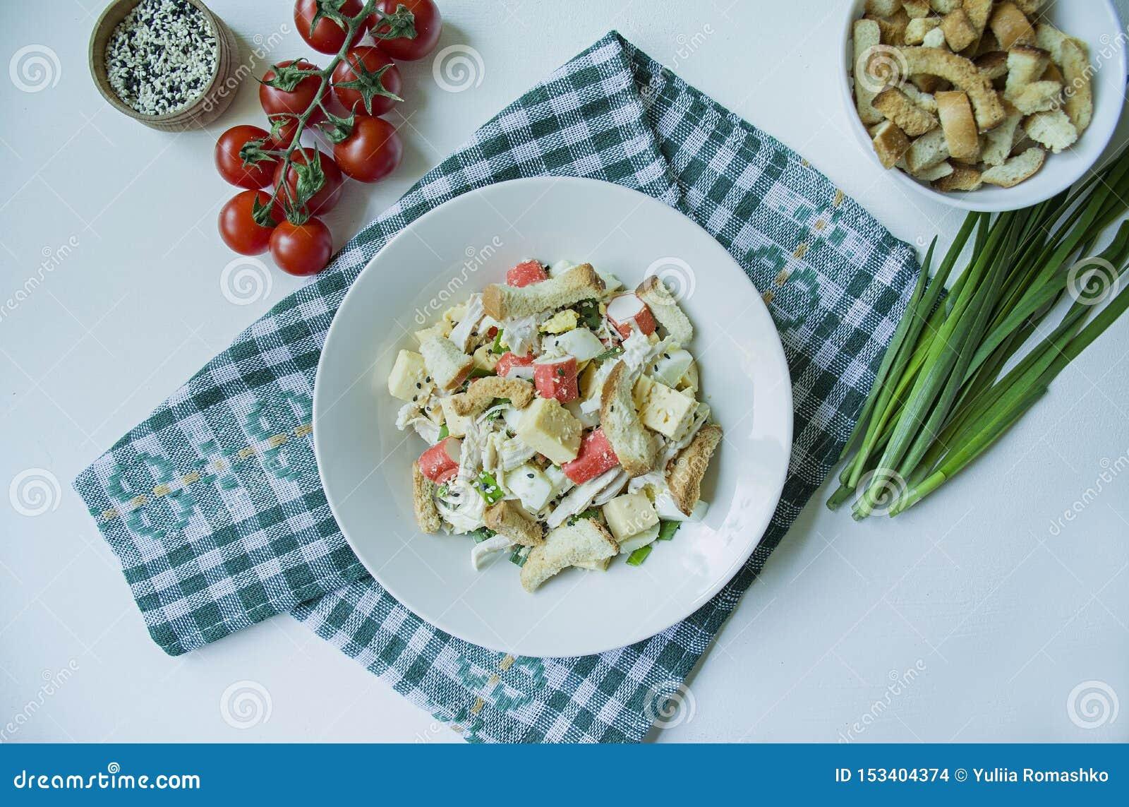 La ensalada con las galletas, los palillos del cangrejo, el prendedero del pollo, las hierbas frescas y el queso duro sazonados c
