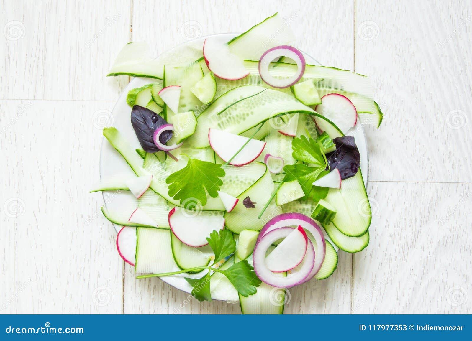 La ensalada verde fresca con el pepino fino cortado, rábano, cebolla roja y albahaca y apio joven se va en el fondo de madera bla