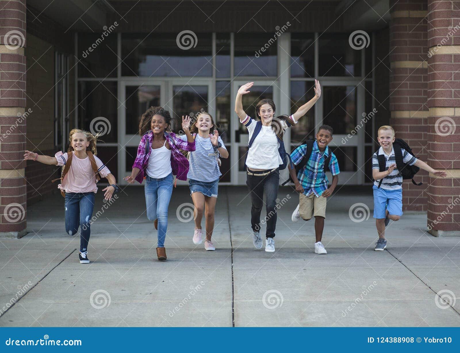 La escuela de la escuela del grupo embroma el funcionamiento mientras que salen de la construcción de escuelas