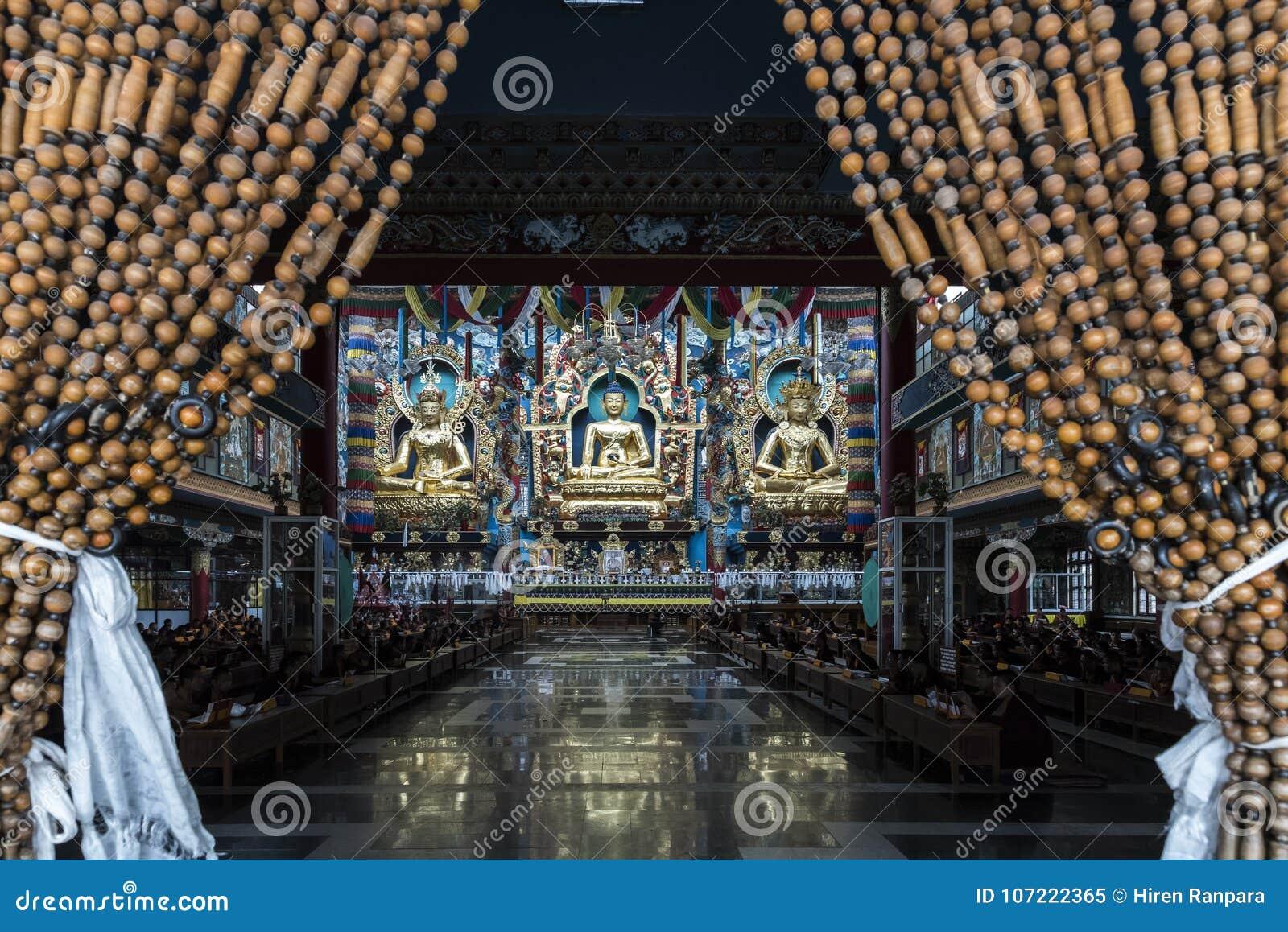 La estatua de Gautam Buddha en centro flanqueó por las estatuas de Padmasambhava en izquierda y de Amitayus en la derecha en el m