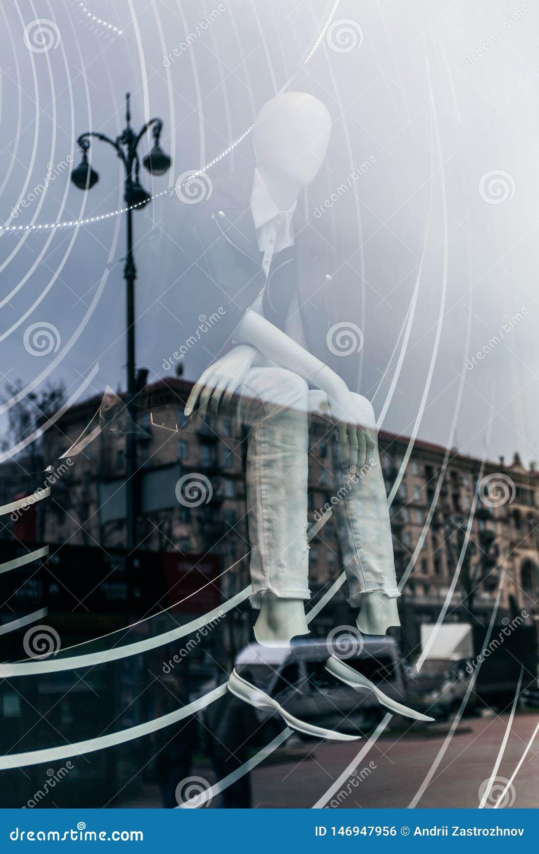 La exposici?n doble es una reflexi?n de la ciudad en la ventana de cristal de la tienda con un maniqu? en ropa de moda