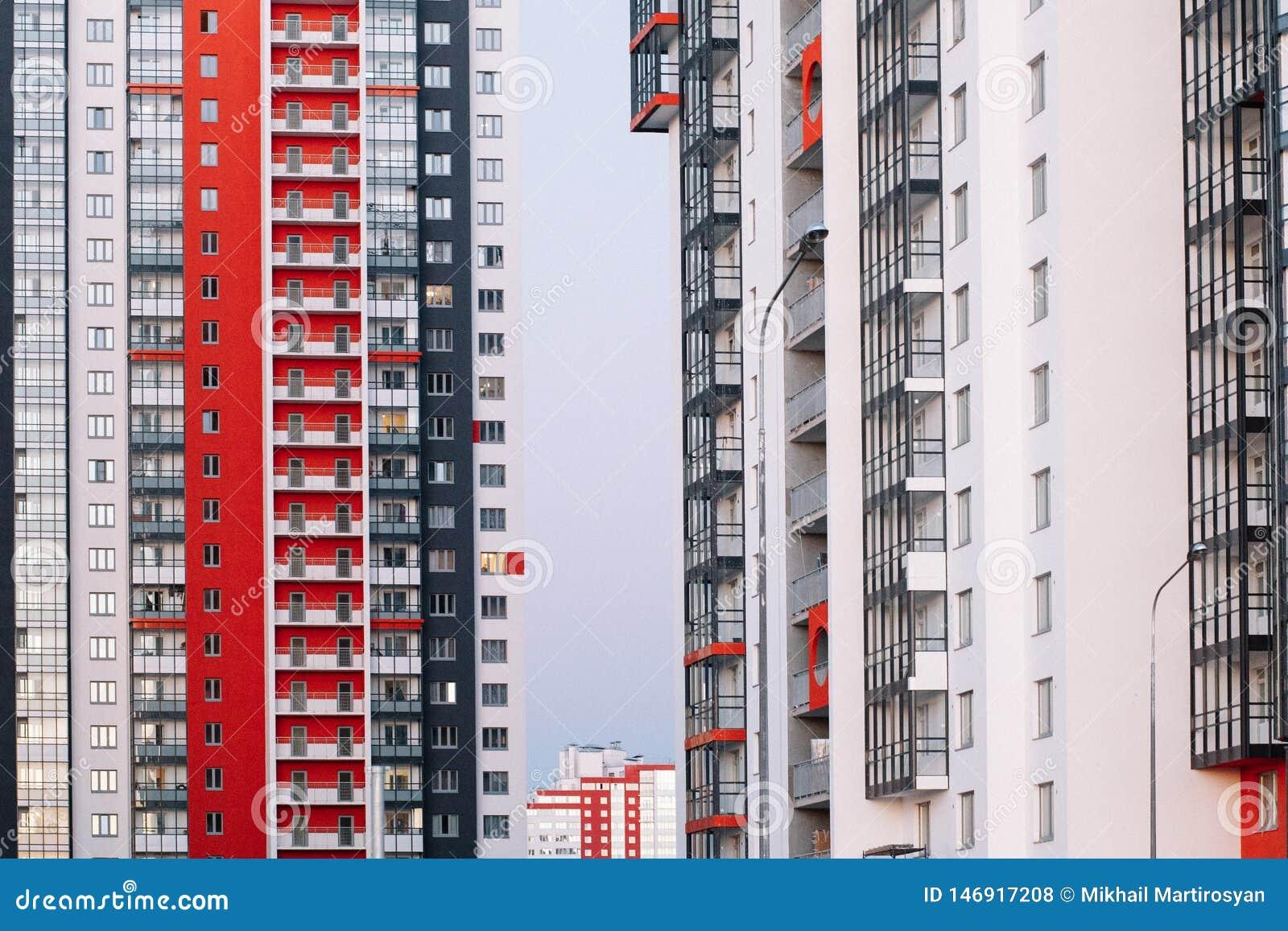 La fachada de un edificio alto con las rayas blancas y grises rojas Edificio de varios pisos contra el cielo azul Fondo a
