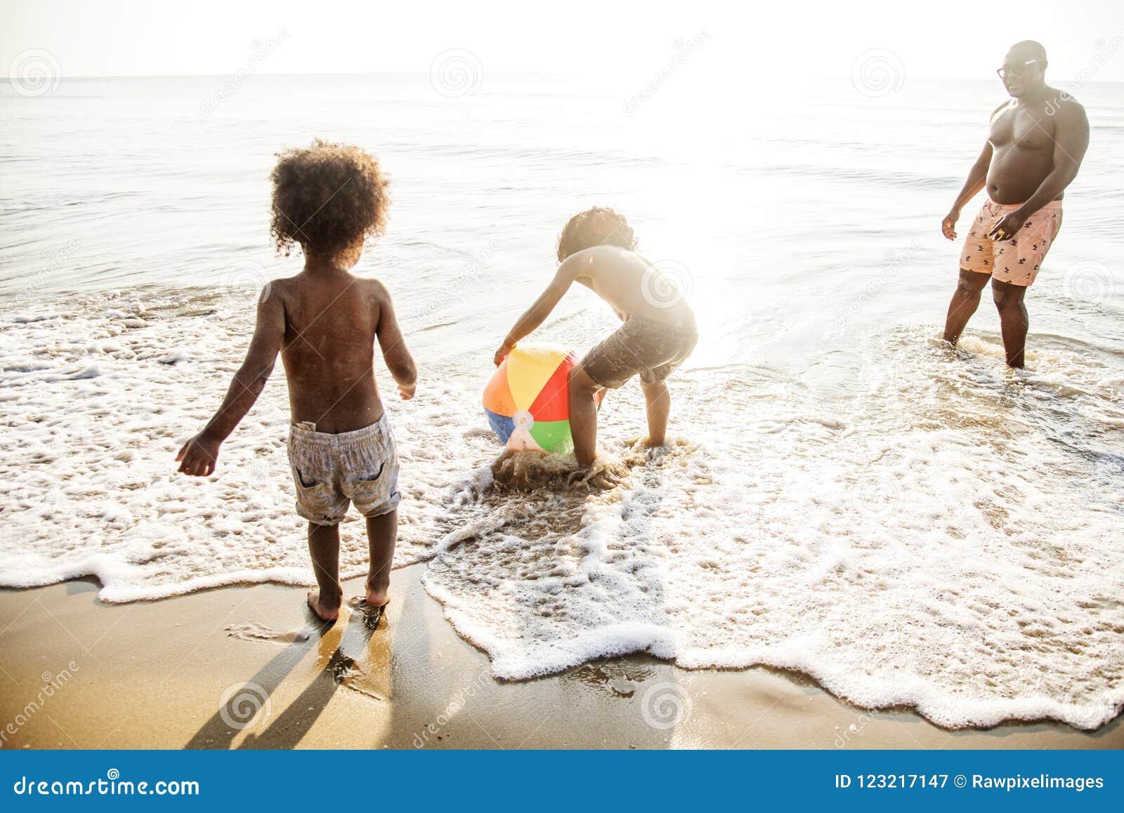 La famiglia africana gode di di giocare la spiaggia