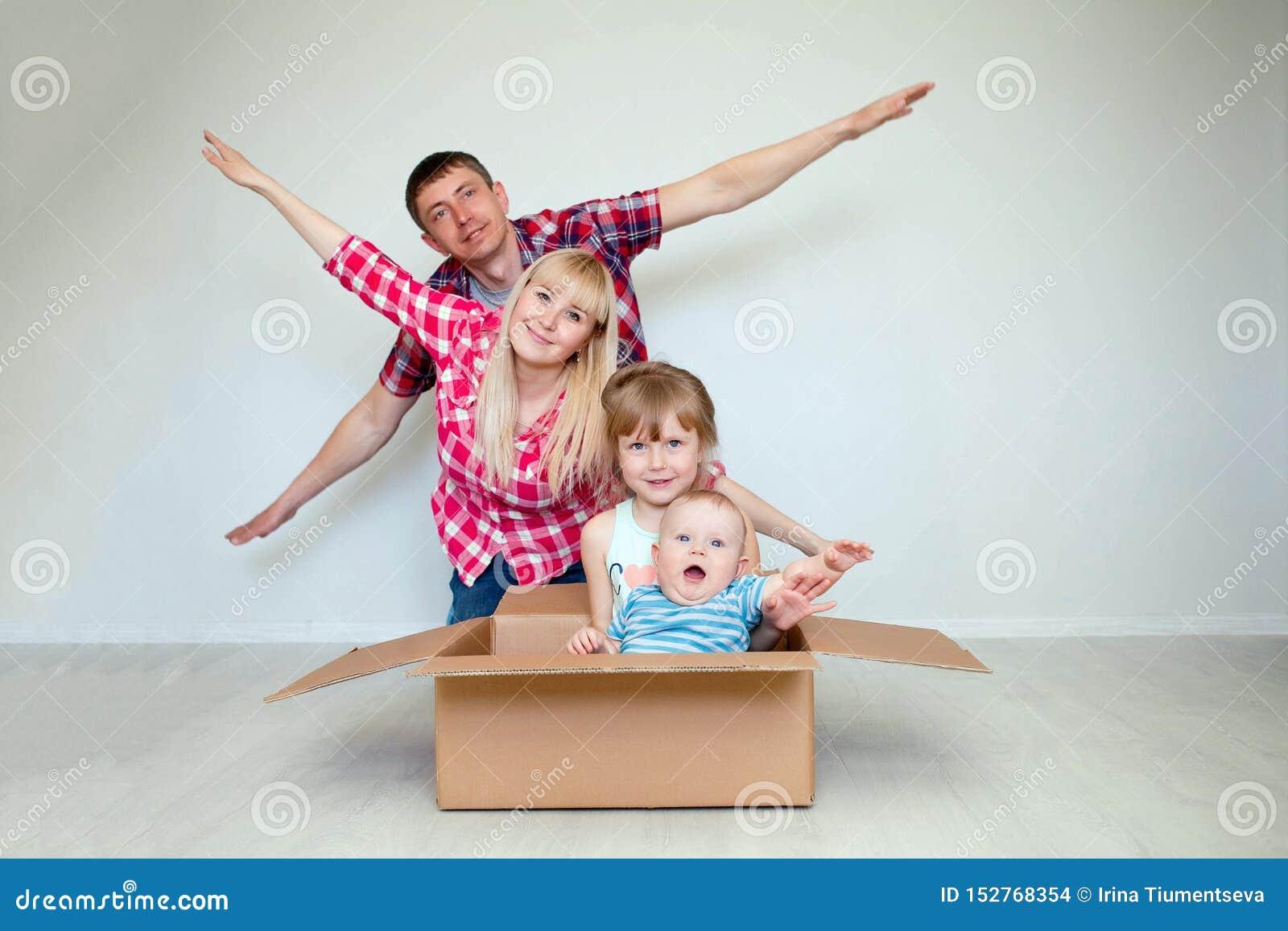 La famiglia felice contro lo sfondo della carta da parati grigia nella stanza vuota, ondeggia una mano, bambini si siede in una s