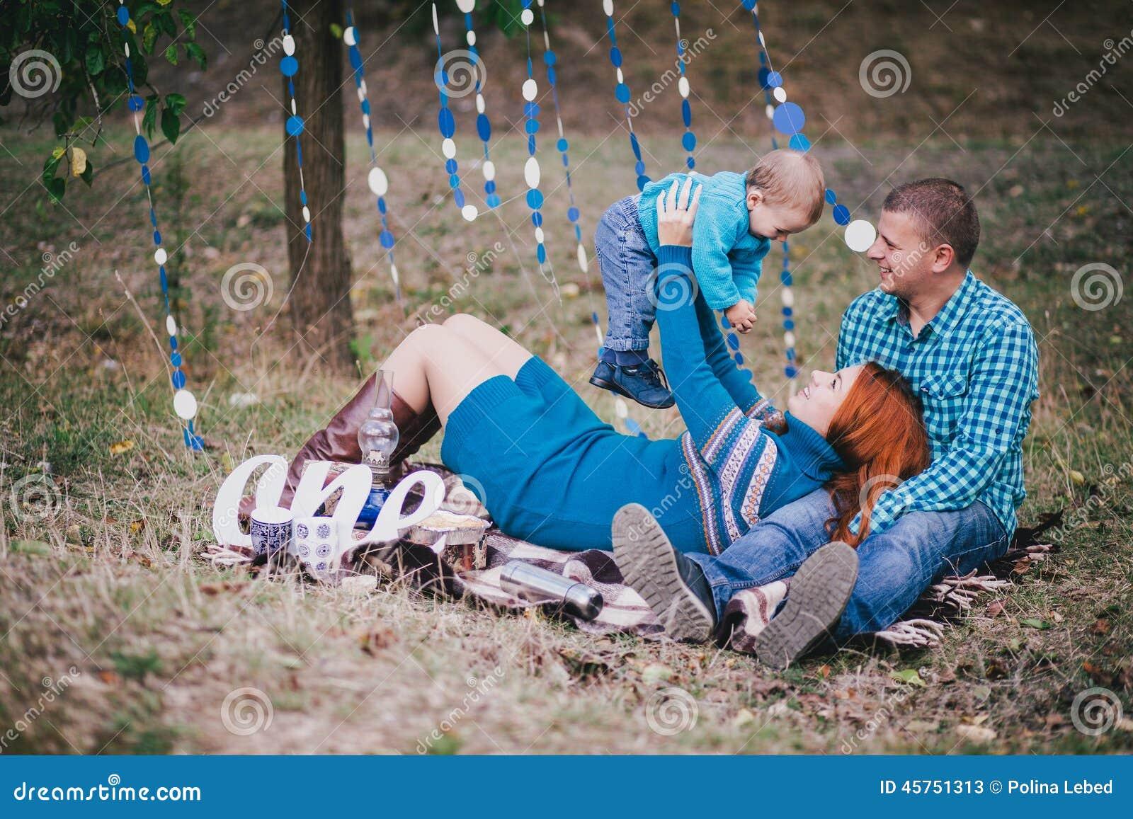 La famiglia felice ha festa di compleanno con le decorazioni blu in foresta