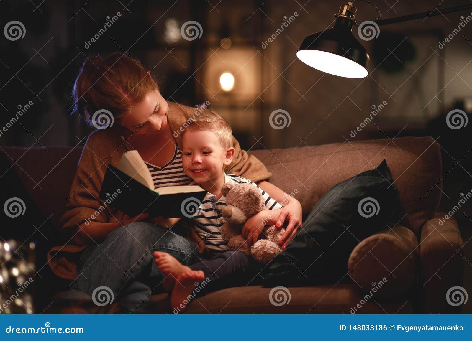 La famiglia prima della madre andante a letto legge al suo libro del figlio del bambino vicino ad una lampada nella sera