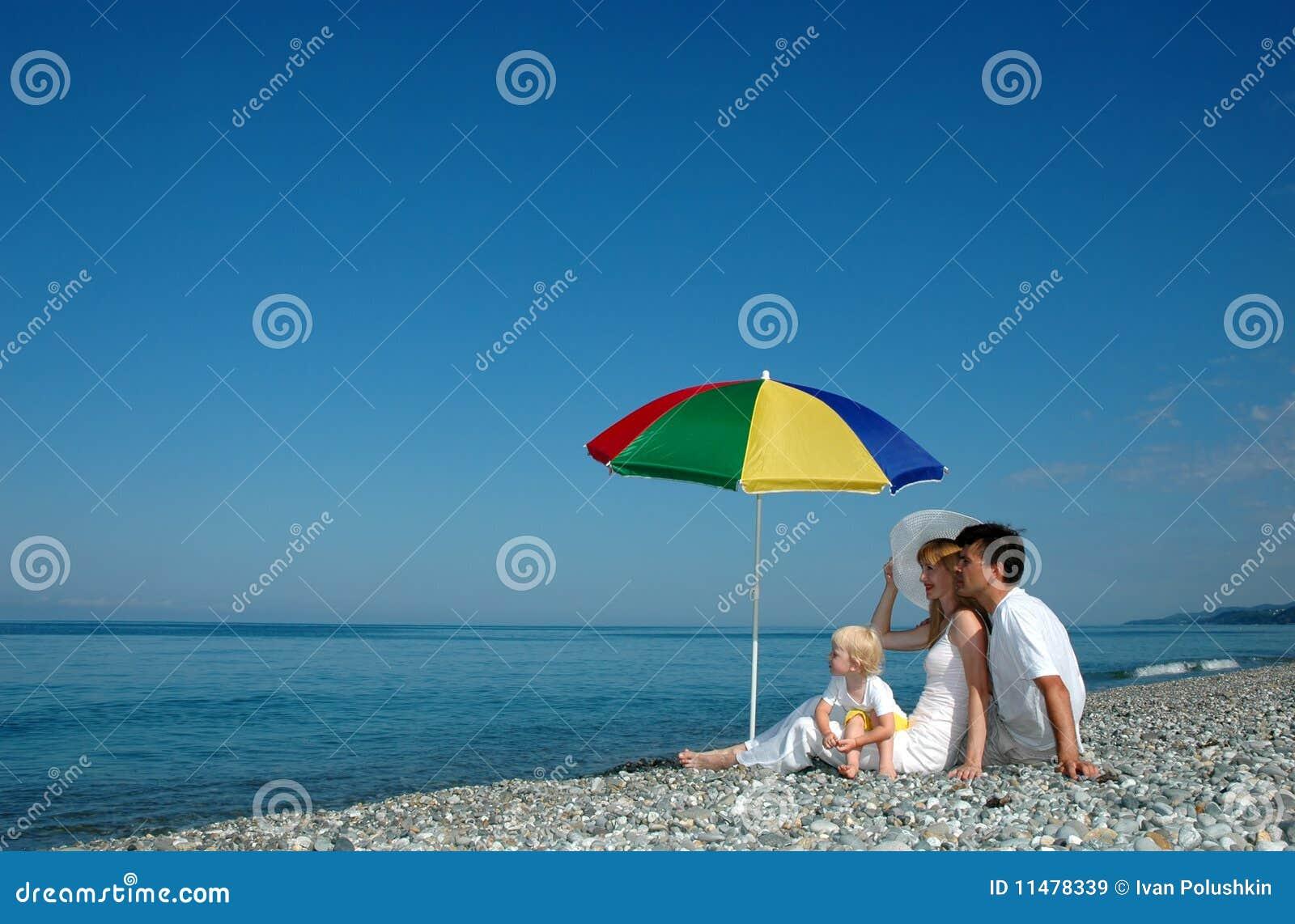La famiglia si siede su una spiaggia