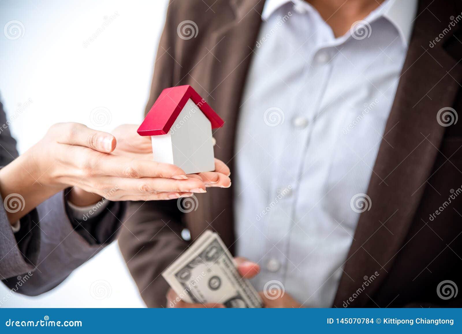 La familia asiática joven del amor de los pares de la felicidad que habla de la compra de la casa y el dueño casero discuten la