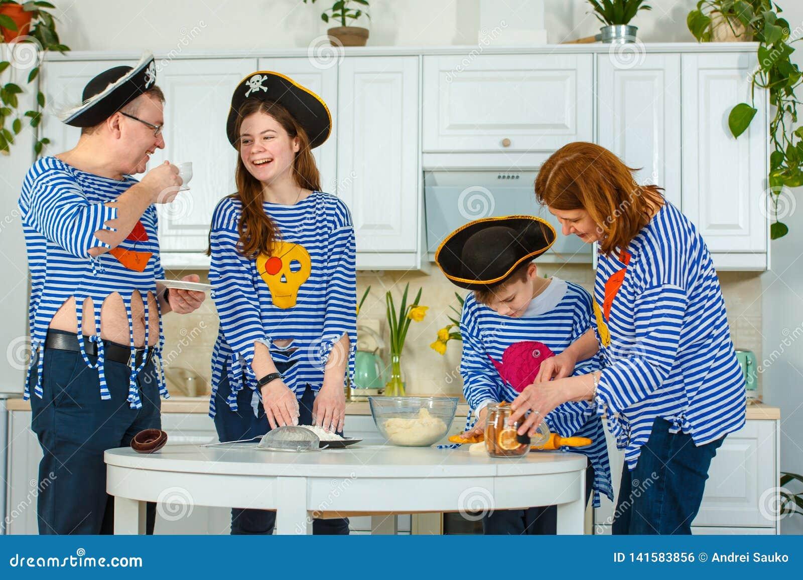 La familia cocina junta Marido, esposa y sus niños en la cocina La familia amasa la pasta con la harina
