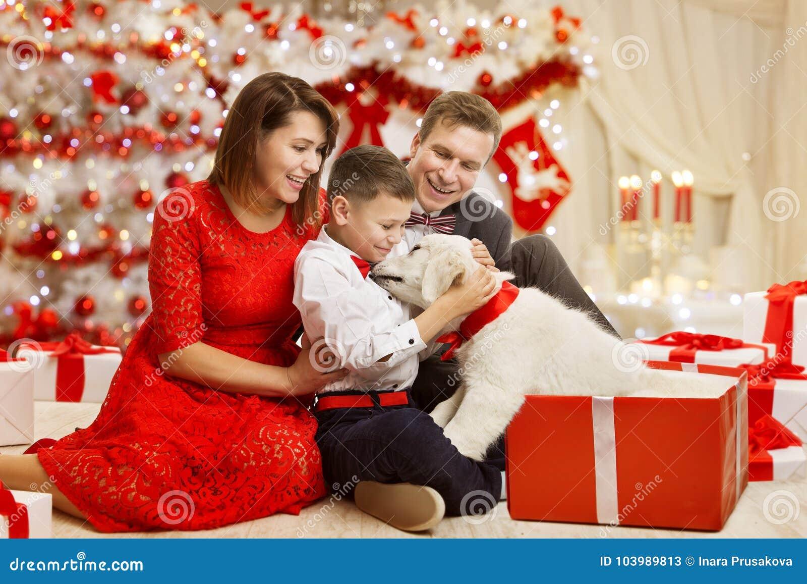 La familia de la Navidad da a perro el actual regalo, celebrando Feliz Año Nuevo