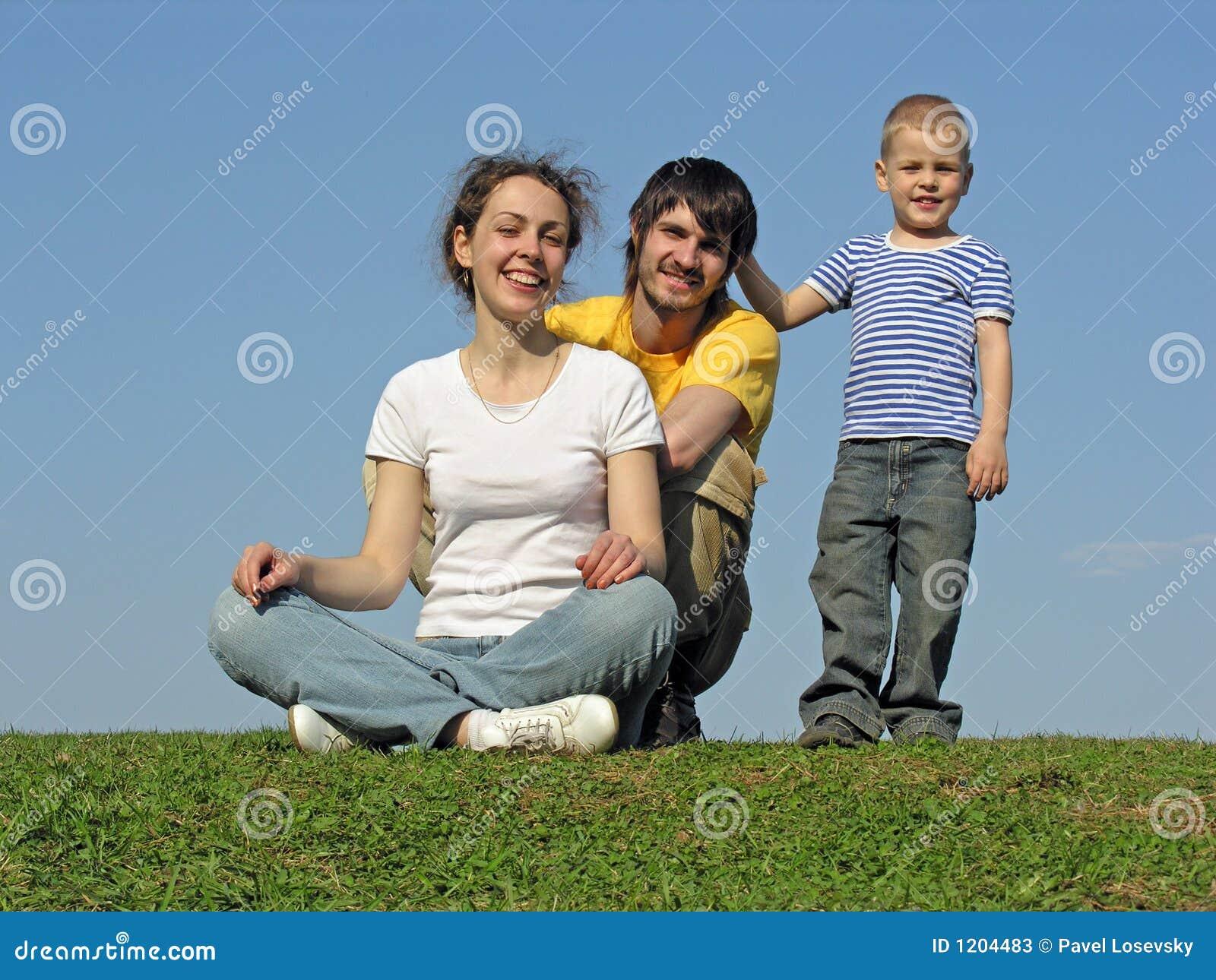 La familia en hierba se sienta