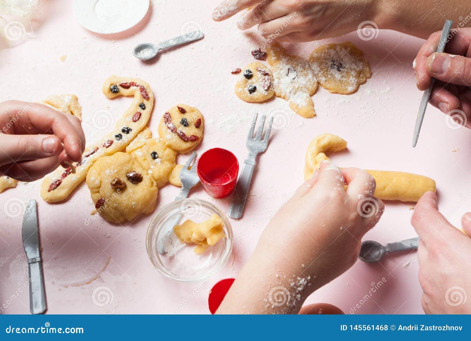 La familia entera está preparando los bollos de la Navidad Galletas de la Navidad y pan de jengibre bajo la forma de muñecos de n