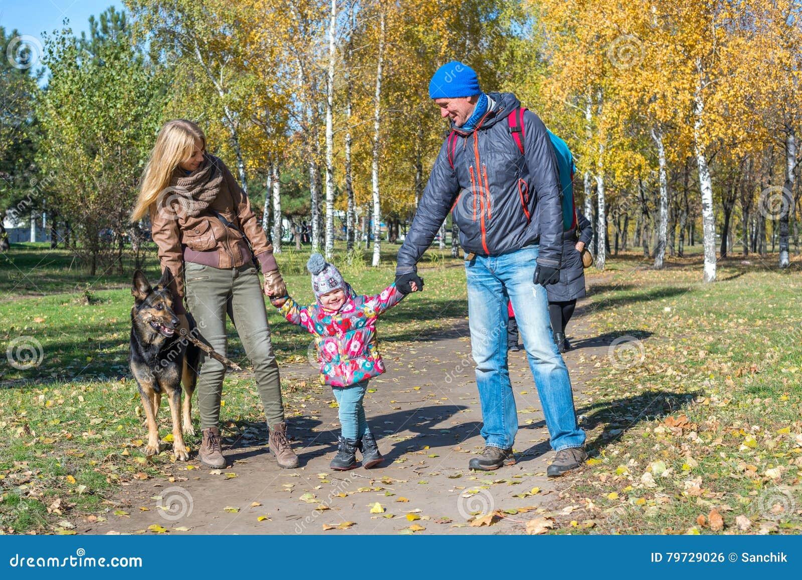 La familia feliz con un perro está caminando