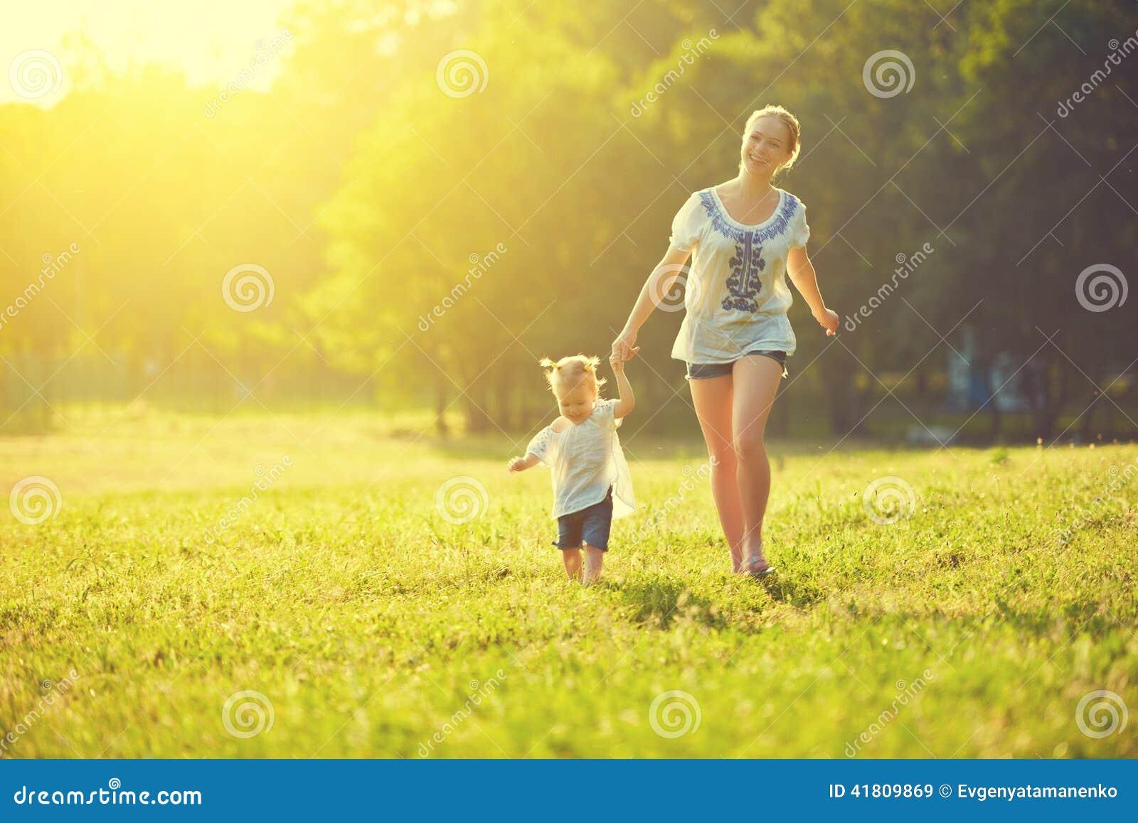 La familia feliz en la naturaleza camina en el verano